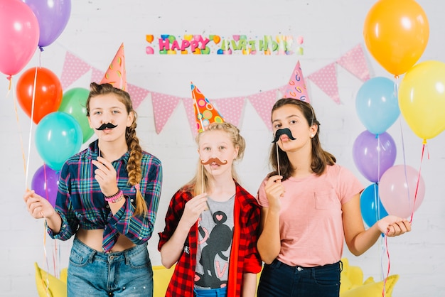 Group of friends posing with prop moustache during birthday Free Photo