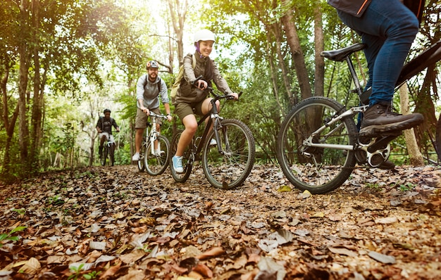 Group of friends ride mountain bike in the forest together Free Photo