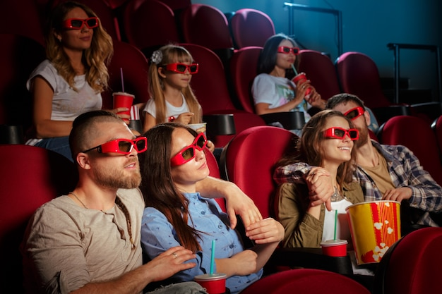 Group of friends sitting in movie theater with popcorn and drinks Premium Photo