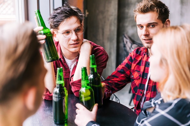 Group of friends sitting together holding green beer bottles Free Photo