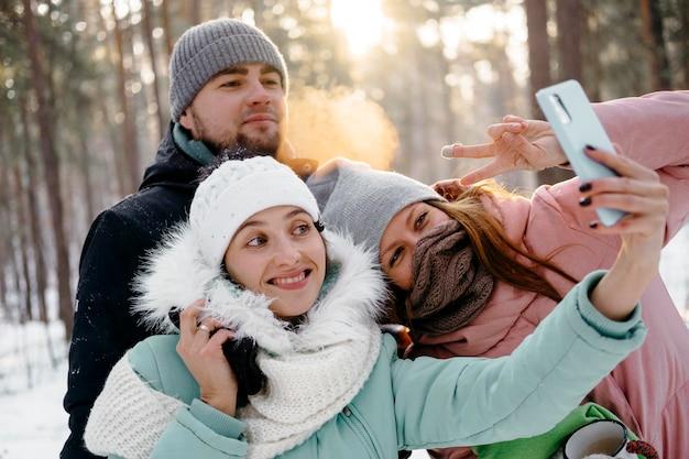 Gruppo di amici che prendono selfie all'aperto in inverno Foto Gratuite