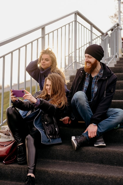 Gruppo di amici che prendono selfie sulle scale Foto Gratuite