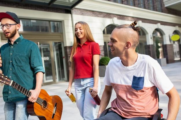 Gruppo di amici che fanno una passeggiata sulla strada della città nel giorno d'estate Foto Gratuite