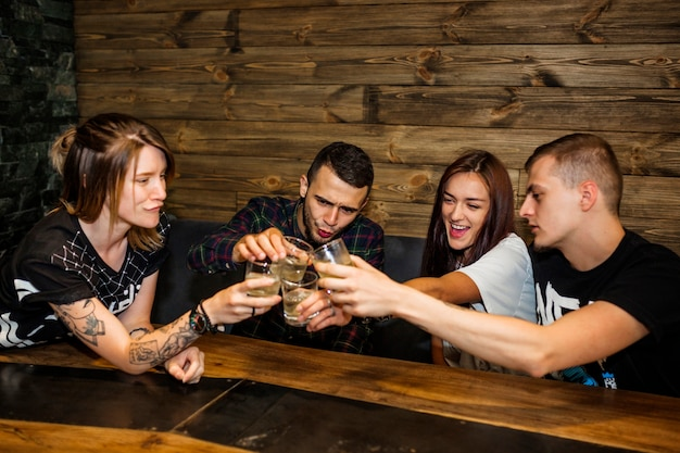 Group of friends toasting glasses of drinks at bar Free Photo