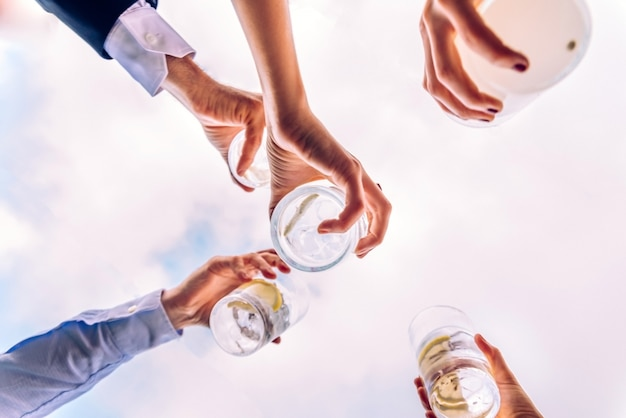 Group of friends toasting with a few glasses of alcohol with the sky in the background Premium Photo