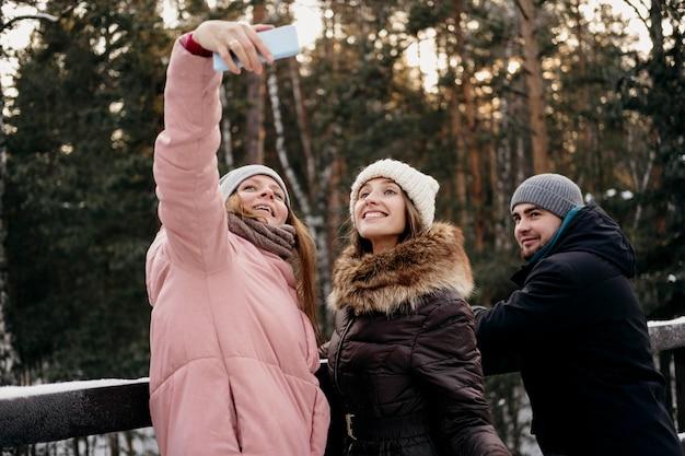 Gruppo di amici che prendono insieme selfie all'aperto in inverno Foto Gratuite