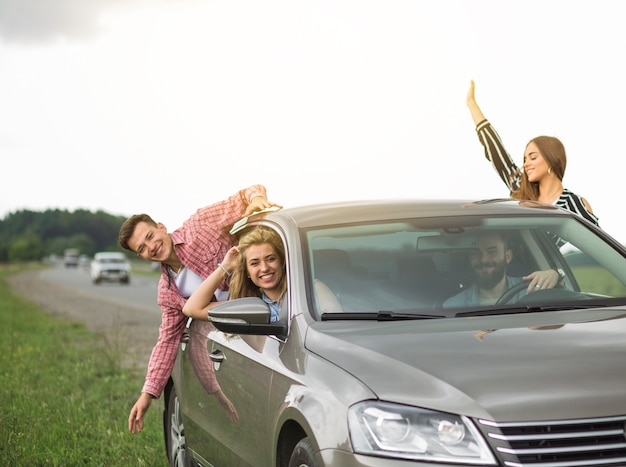 Group of friends travelling in the car hanging out through open window Free Photo