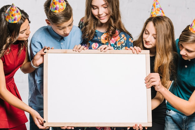 Group of friends wearing party hat looking at white blank frame hold by them Free Photo
