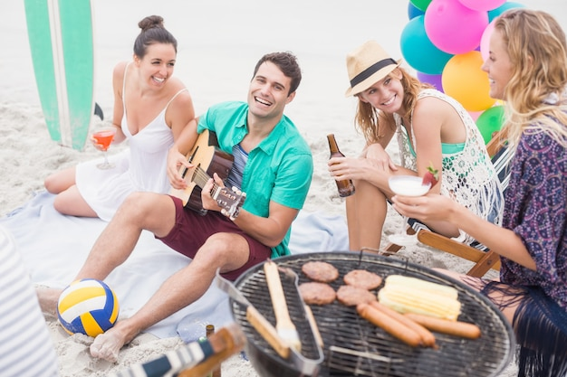 Group of friends with drinks and guitar sitting next to a barbecue Premium Photo