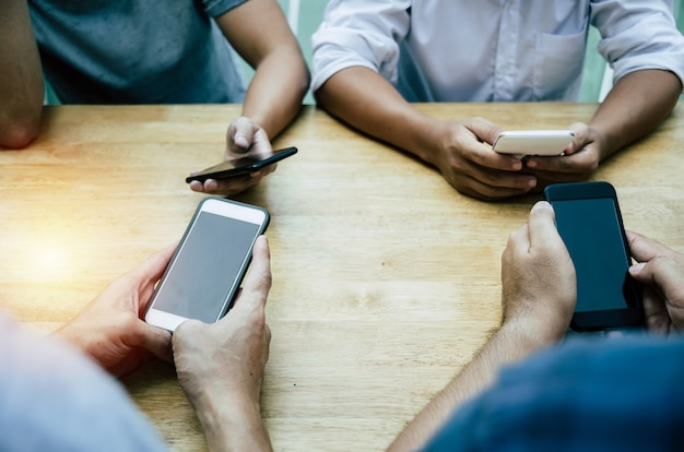 Group of friends or young people hands using smart phone playing social networking Premium Photo