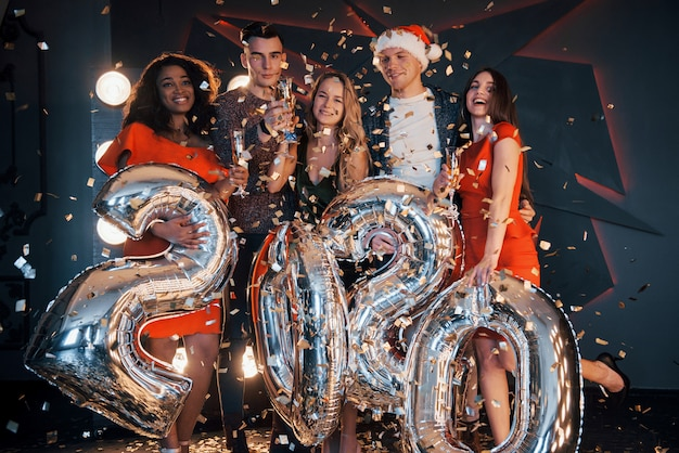 A group of fun young beautiful multinational people throwing confetti at a party. celebration of 2020. Premium Photo
