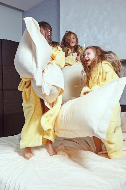Gruppo di amiche che prendono tempo goog sul letto. bambini che ridono felici girsl che giocano sul letto bianco in camera da letto Foto Gratuite
