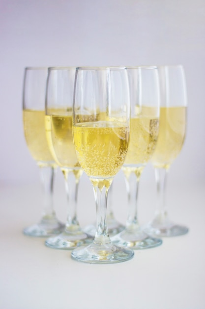 A group of glasses with champagne on a white background. Premium Photo