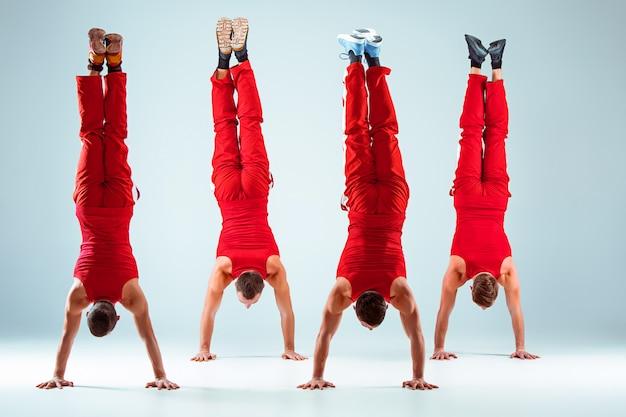 Gruppo di uomini caucasici acrobatici relativi alla ginnastica sulla posa dell'equilibrio Foto Gratuite