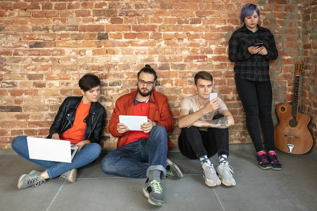 Group of happy caucasian young people behind the brick wall. Free Photo