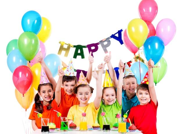 Gruppo di bambini felici in camicie colorate divertendosi alla festa di compleanno - isolato su un bianco Foto Gratuite