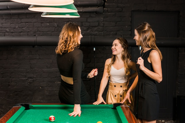 Group of happy female friends standing near snooker table Free Photo
