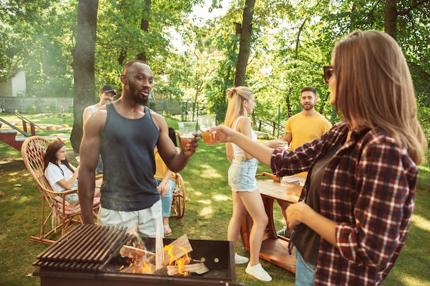Group of happy friends having beer and barbecue party at sunny day. resting together outdoor in a forest glade or backyard. celebrating and relaxing, laughting. summer lifestyle, friendship concept. Free Photo