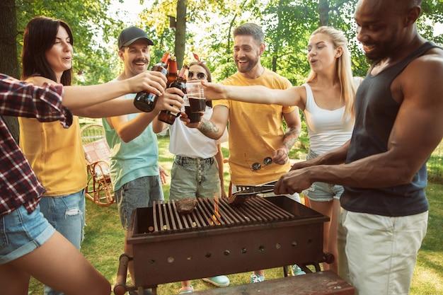 Gruppo di amici felici che hanno birra e barbecue party in giornata di sole. riposare insieme all'aperto in una radura della foresta o in un cortile Foto Gratuite