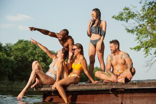 Gruppo di amici felici divertendosi e ridendo sul molo sul fiume. Foto Gratuite