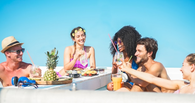Group of happy friends making boat summer party with tropical cocktails Premium Photo