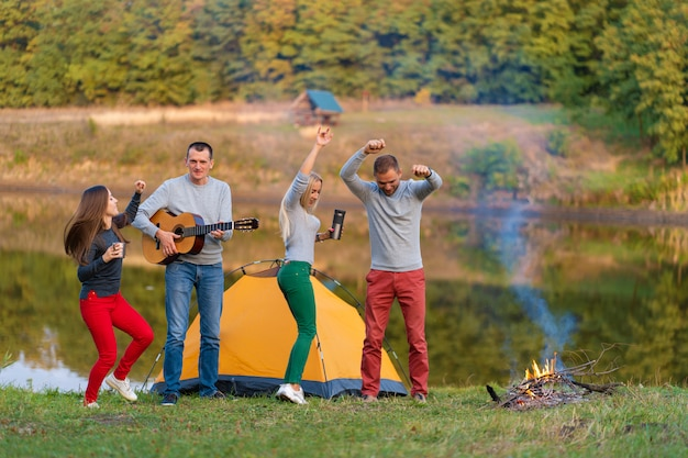 Group of happy friends with guitar, having fun outdoor, dancing and jumping near the lake in the park background the beautiful sky. camping fun Premium Photo