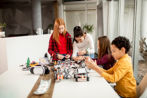 Group of happy kids programming electric toys and robots at robotics classroom Premium Photo