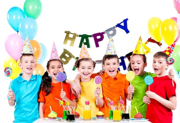 Gruppo di bambini felici con caramelle colorate divertendosi alla festa di compleanno - isolato su un bianco Foto Gratuite