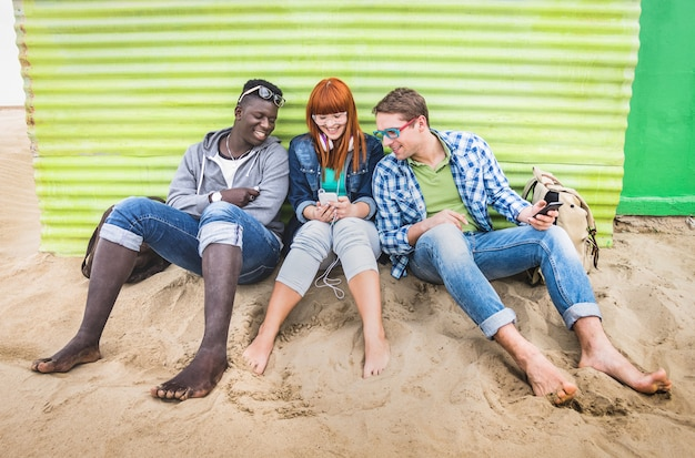 Group of happy multiracial friends having fun together using mobile smart phone Premium Photo