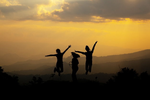 Group of happy people jumping in the mountain at sunset Free Photo