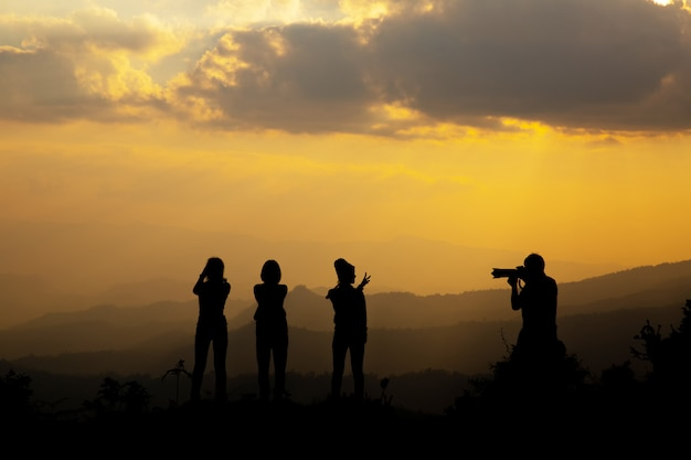 Group of happy people photographing in the mountain at sunset Free Photo