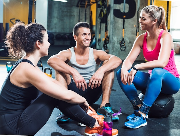 Group of happy people taking break after workout in gym Free Photo