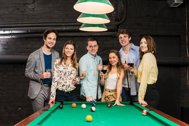 Group of happy smiling friends with drinks standing behind snooker table Free Photo