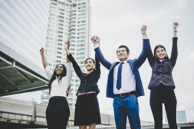 Group of happy young business people with hands in the air success on their plans. Free Photo