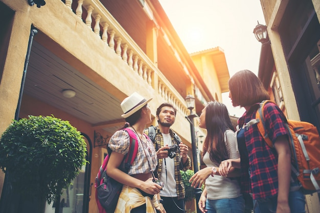 Group of happy young friends having fun walking in urban street. friendship travel concept. Free Photo