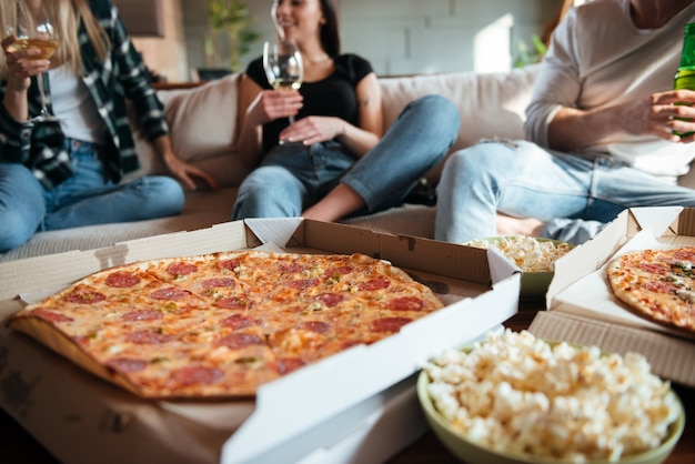Group of happy young people eating pizza, drinking wine and beer on sofa at home Premium Photo