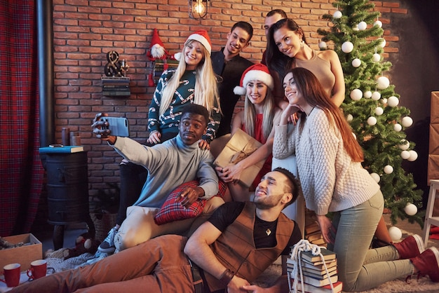 Group of ã'âheerful old friends communicate with each other and make a selfie photo. new year is coming. celebrate the new year in a cozy home atmosphere Premium Photo