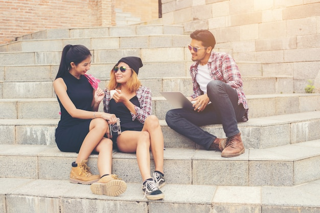 Group of hipster students sitting on a staircase talking and rel Free Photo
