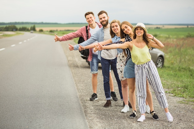 Group of hitchhikers waiting for car on countryside road Free Photo