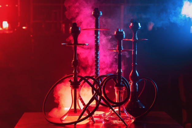 Group of hookahs with shisha coals in bowls on a red and blue background with smoke Premium Photo