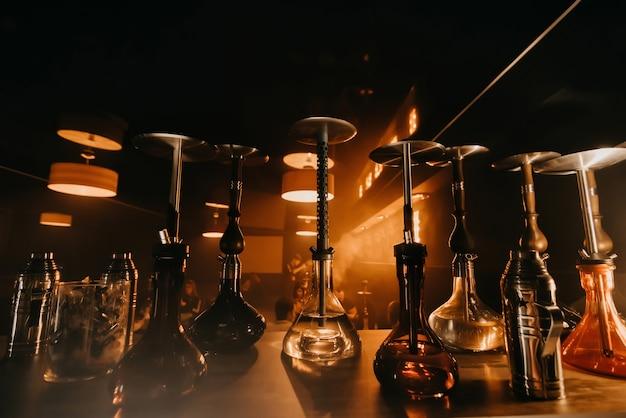 Group of hookahs with shisha glass flasks and metal bowls Premium Photo