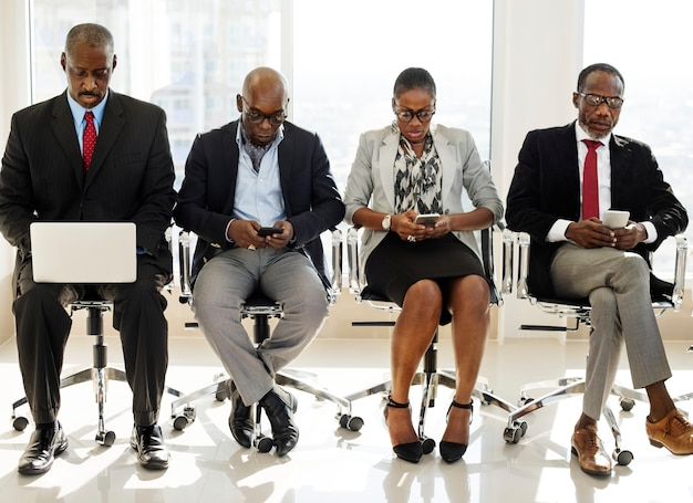 A group of international business people are sitting and using wireless devices Premium Photo