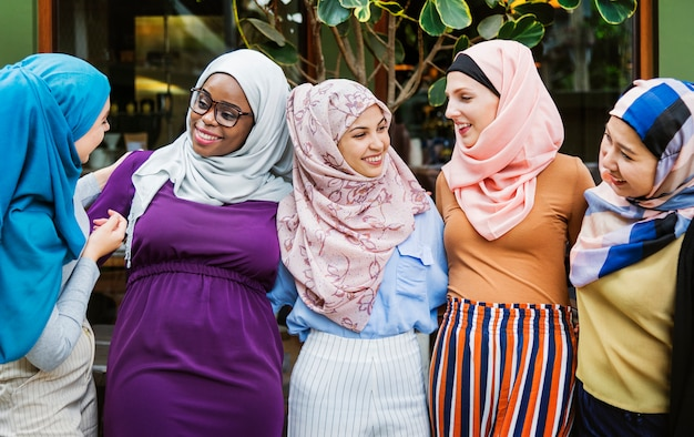 Group of islamic friends arms around and smiling together Premium Photo