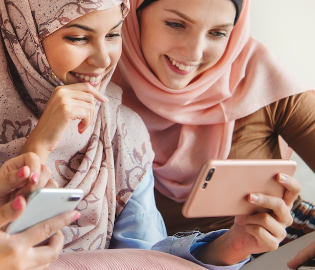 Group of islamic women talking and watching on the phone together Premium Photo