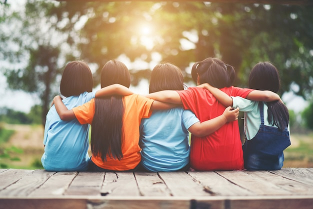 Group of kids friends arm around sitting together Free Photo