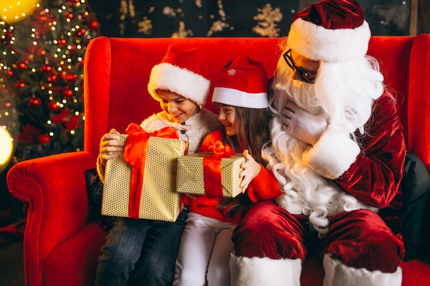 Group of kids sitting with santa and presents on christmas eve Free Photo