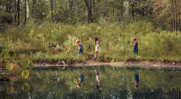Group of kids walking through a field covered in greenery and reflecting on the lake under sunlight Free Photo
