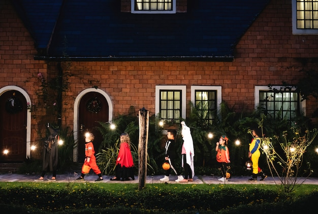 Group of kids with halloween costumes walking to trick or treating Free Photo