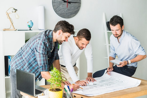 Group of male architect preparing blueprint in office Free Photo