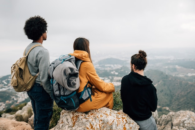 Group of male and female hiker sitting on rock looking at mountain view Free Photo